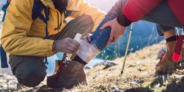 Man taping up woman's ankle on a hike