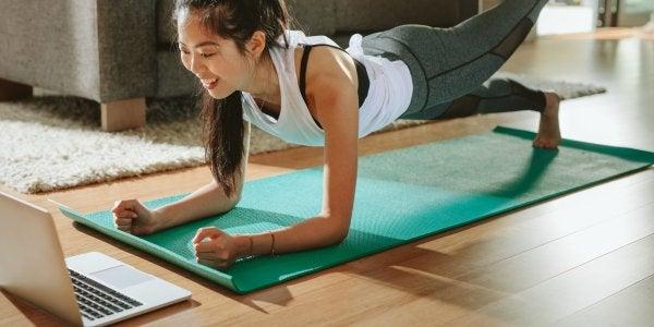 woman on yoga mat watching laptop