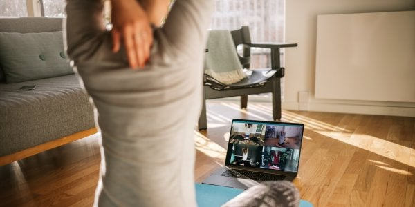 woman working out at home looking at her laptop