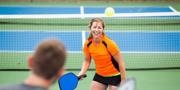 A guy and a girl playing pickleball at a tennis court