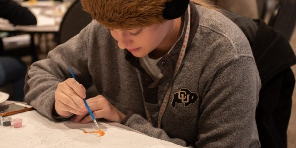 student in CU gear painting