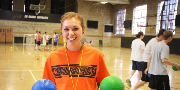 smiling woman holding dodgeballs