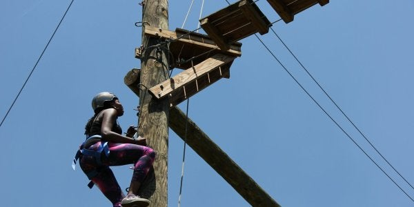 Female student climbing up post at the Challenge Course
