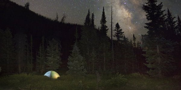 Camping tent lit up at night under stars