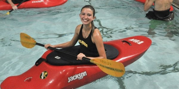 Female student smiling in a kayak in the pool