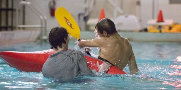 Student learning to roll a kayak in the pool