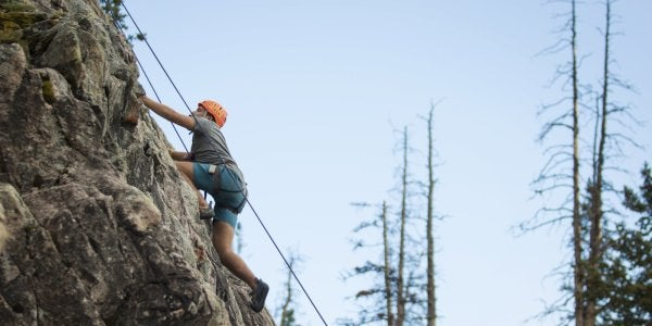 Student climbing outdoors with belay