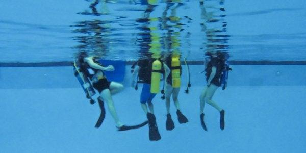 People in pool with scuba gear