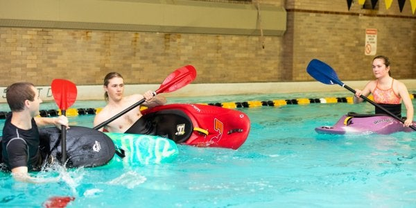 Students practicing kayak rolls in the pool