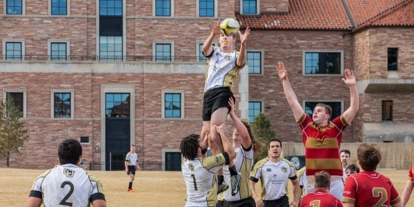 Men's rugby team throwing player in air