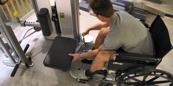 man in wheelchair using weights