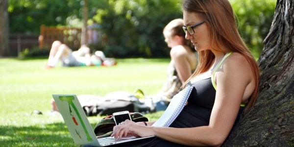 woman on her laptop underneath a tree