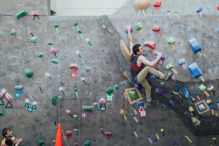 Male student bouldering in the climbing gym.