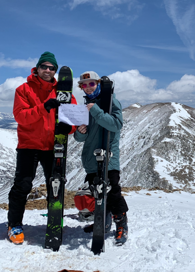 two men with skis and a sign at the top of a snowy mountain