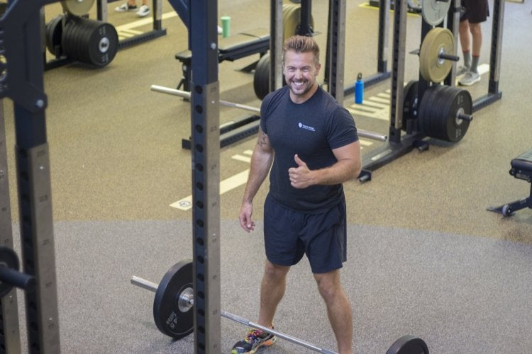 Personal Trainer giving a thumbs up next to barbells in the weight room