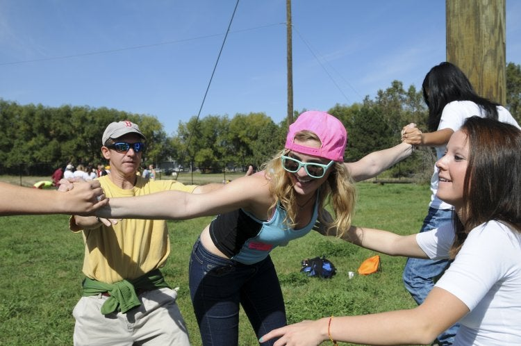 students laughing as they do the challenge course