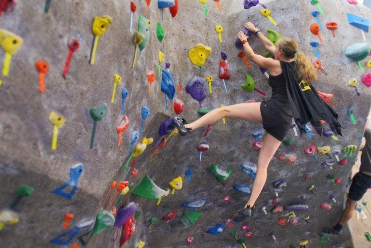 woman in a batman cape climbing a wall