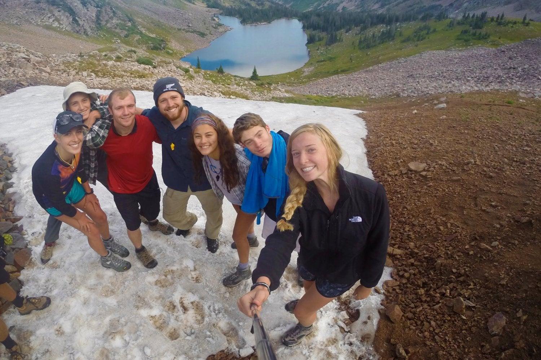 Hikers posing as group above lake