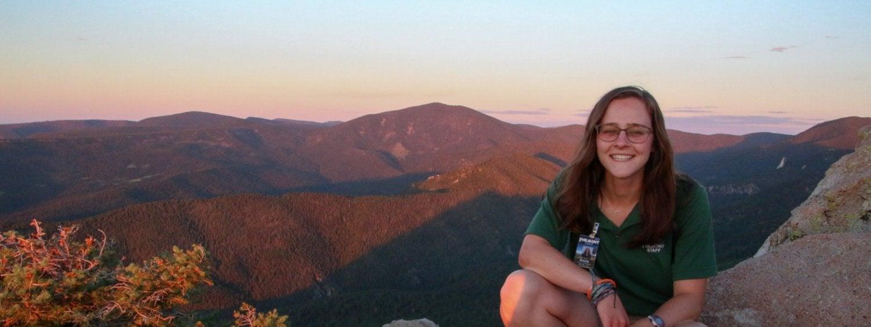 woman sitting on cliffs edge overlooking a mountain range