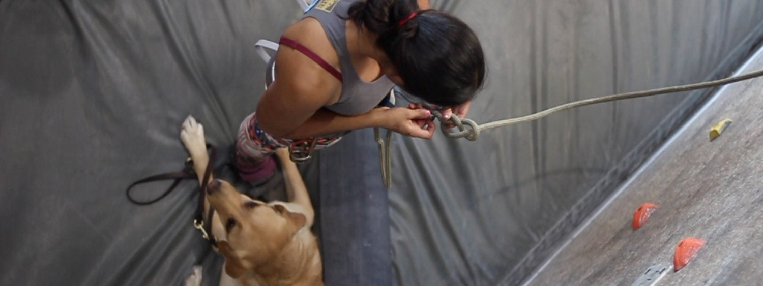 Woman climbing with dog