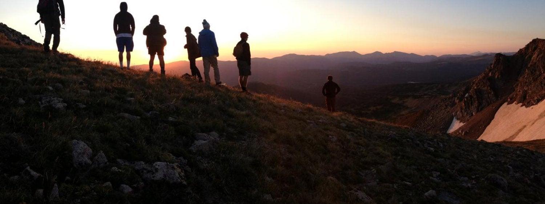 students on mountain at sunset