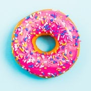 Donut with pink frosting and sprinkles.