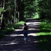 lone woman running through a trail in the forest