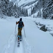woman on cross country skis moving through a snowy pass
