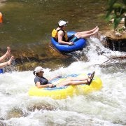 4 tubers floating down a small rapid