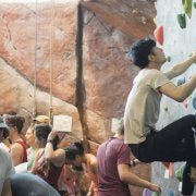 One person bouldering on the climbing wall, others standing near them