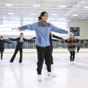 five women ice skating in the rec