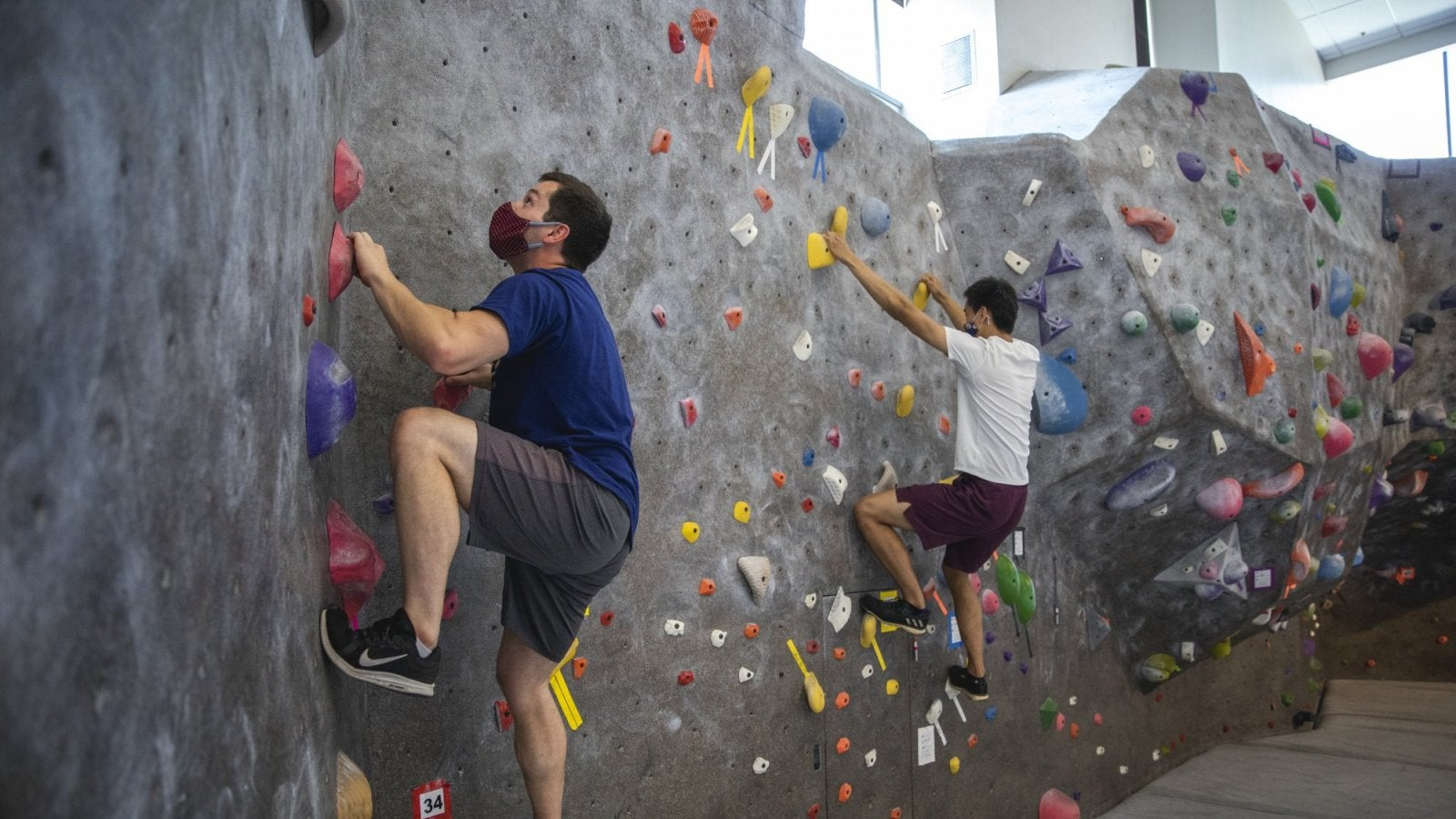 two men in masks climbing a wall