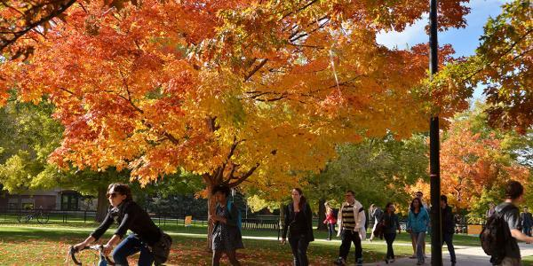 Students walk and bike across campus with fall foliage in the background.