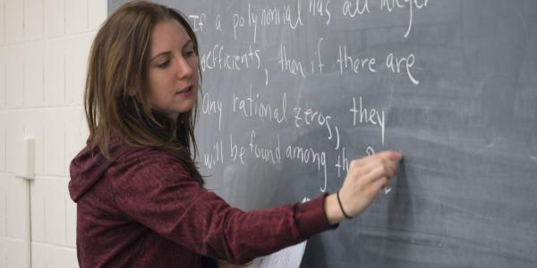 An instructor writing on a chalkboard.