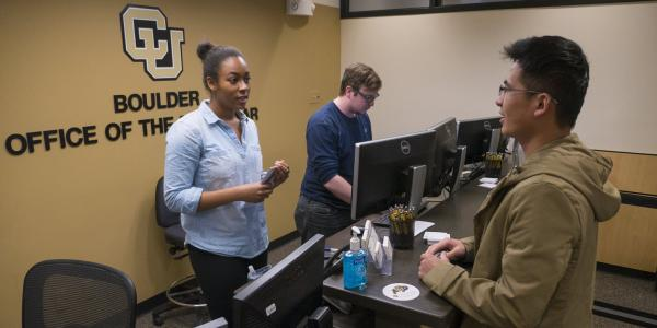 Two Office of the Registrar student employees help a student at the reception desk