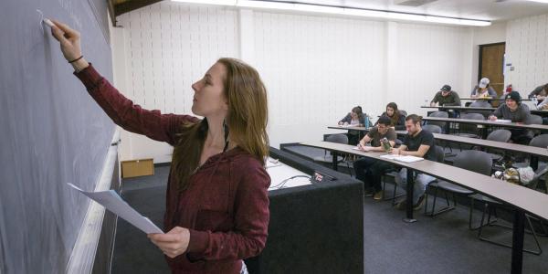 An instructor writes on a chalkboard.