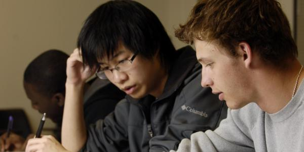 Two students work together on a written assignment.