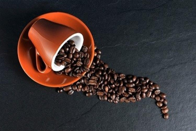 Image of coffee cup spilling coffee beans