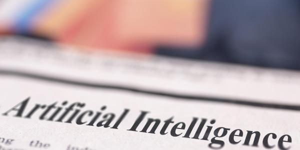 A photo of a newspaper with a headline that reads artificial intelligence.
