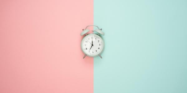 An alarm clock on colored background