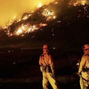 Firefighters stand in front of wildfire