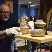 Researcher with Native American pottery in the Museum of Natural History