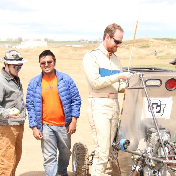 Bill, Coach, and Rishav working on the car
