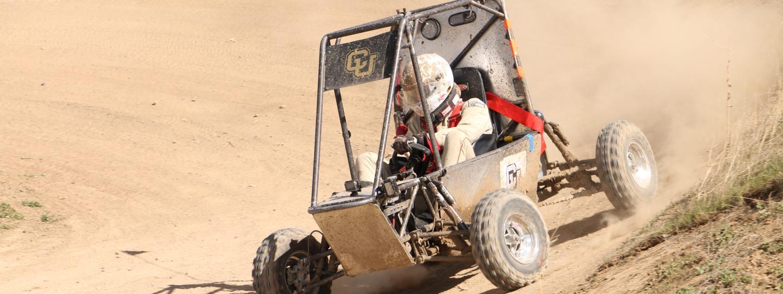 Car driving on dirt berm
