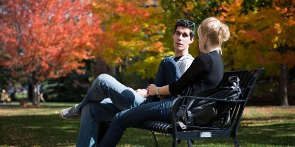 Two people having a conversation on a bench outdoors