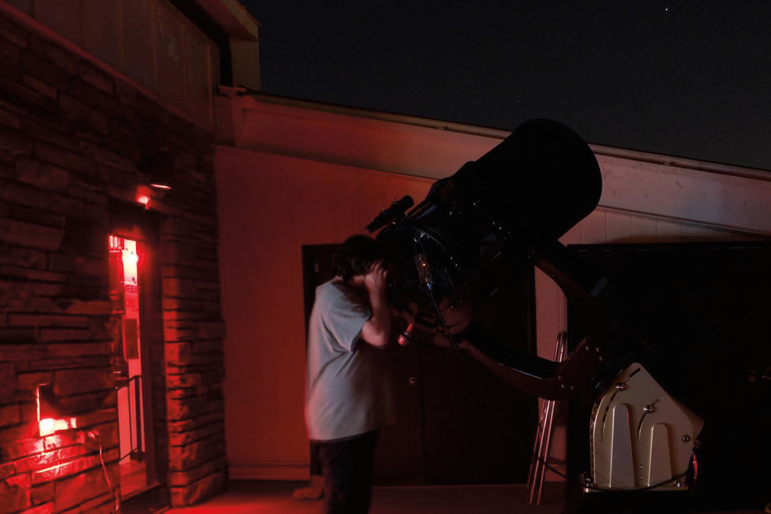 Person looking through a PlaneWave telescope at night with red lights