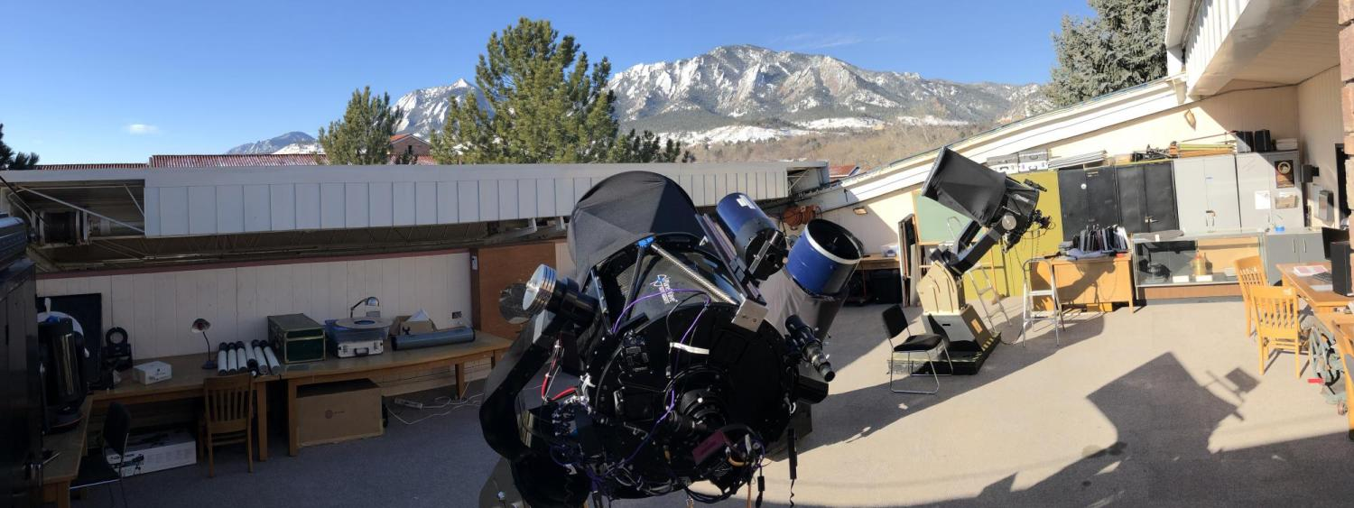 Photo of observing deck at SBO with many telescopes, Flatiron mountains visible in background with snow