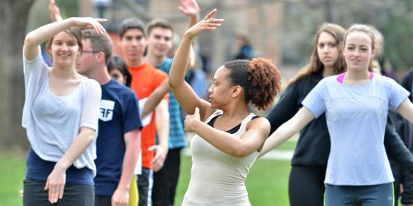 student teaching dance class on campus lawn, arms raised