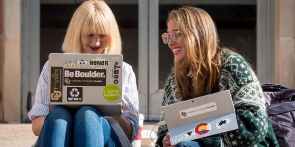 two students sitting on bench smiling, conversing, and looking at their laptops