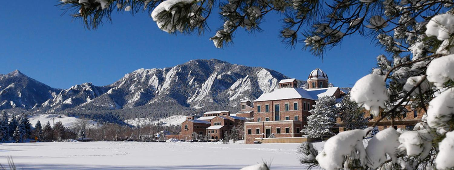 CU Boulder campus in the snow with flatirons